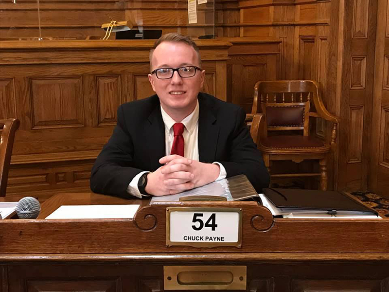 Photo of Zackery Brandenburg sitting at Senator Chuck Payne's desk