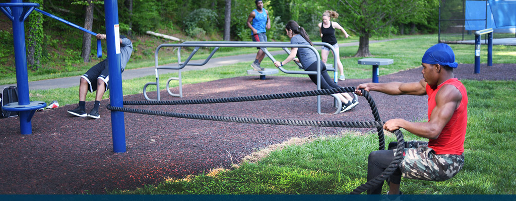 Photo of student working out on outdoor fitness equipment